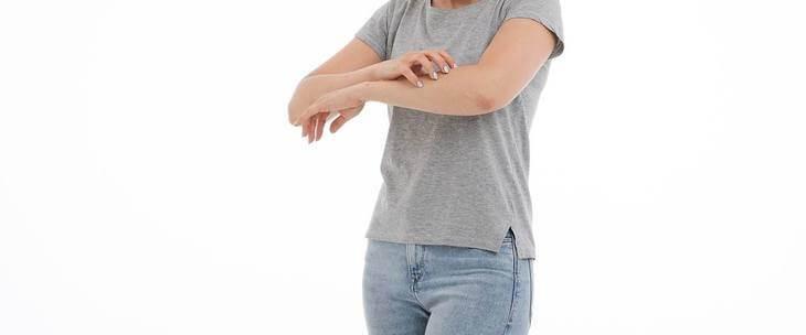 Devojka koja se češa po ruci