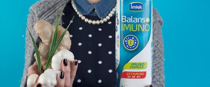 Žena koja drži u jednoj ruci đumbir i luk, a u drugoj Balans imuno jogurt