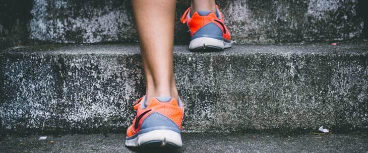 Noge i patike za trčanje koje se penju uz stepenice