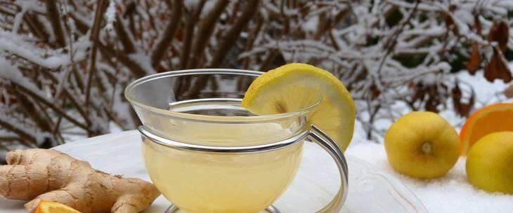 Šolja čaja sa limunom na terasi i sneg napolju
