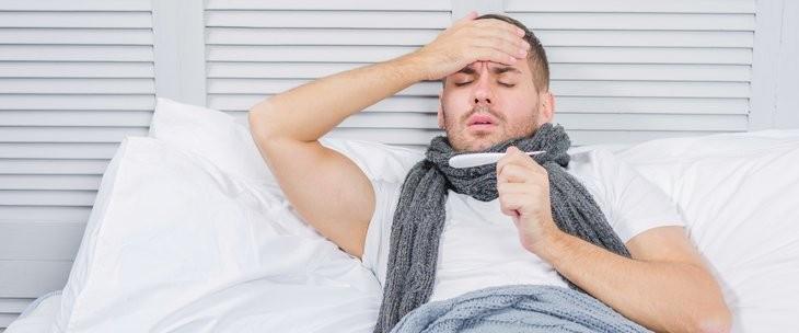 Prehlađen muškarac leži u krevetu