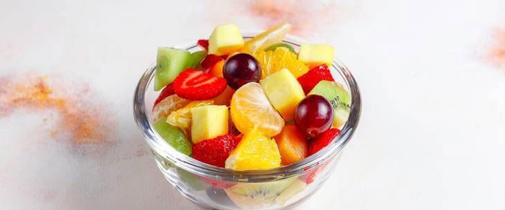 Činija sa voćem u kojoj se nalaze mandarine, jagode, grožđe i ostalo zdravo voće